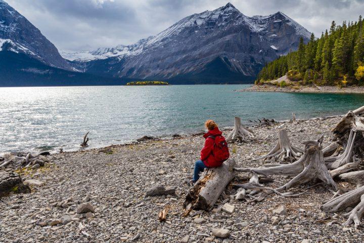Frau mit Rucksack am Seeufer