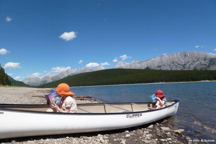 Kinder im Kanu am Ufer eines Wildnissees