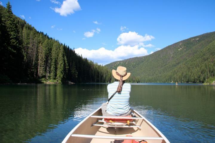 Frau im Kanu auf Fluss durch den Wald